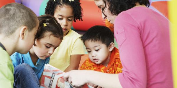 A group of children crowded around an adult reading
